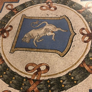 mosaics portraying the coat of arms of four capitals of the Kingdom of Italy. Tradition says that if a person spins around three times with a heel on the testicles of the bull from Turin coat of arms this will bring good luck.